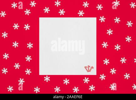 Maquette avec des flocons de Noël sur fond rouge. Bonne année. L'espace pour le texte. Concept d'hiver. Carte de vœux. L'espace de copie, modèle. Vue d'en haut