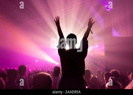 Silhouette d'une femme tandis que la danse s'est assis sur les épaules de quelqu'un à un concert de musique avec éclairage magenta vif Banque D'Images