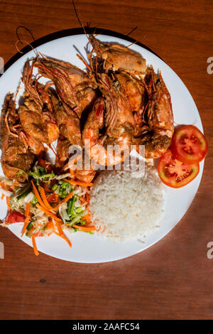 Langoustines avec accompagnement et salade sur une table en bois. Close-up. Banque D'Images