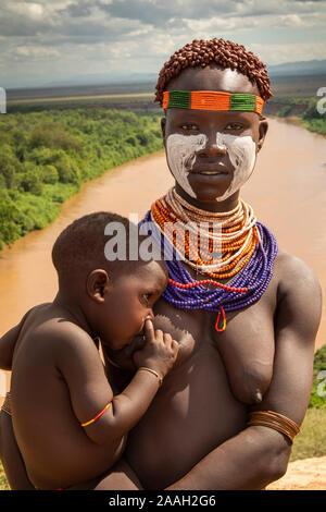 L'Éthiopie, de l'Omo, Kolcho village au-dessus de la rivière Omo, traditionnellement vêtus femme avec tribal Karo l'allaitement du jeune enfant Banque D'Images