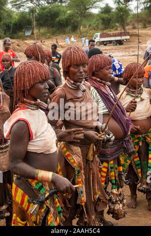 L'Éthiopie, de l'Omo, Turmi, bull jumping cérémonie, Hamar femmes tribales en attente de flagellation rituelle holding propres whips en bois Banque D'Images