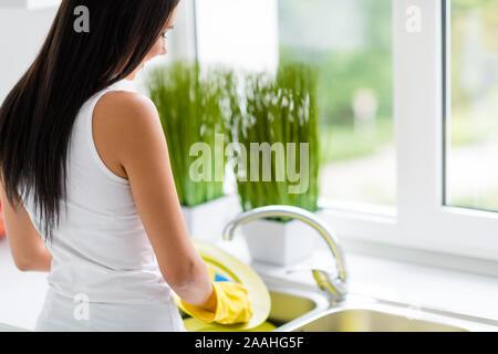 Retour arrière photo de cheerful girl positive rester près de l'impression de faire la vaisselle confort fenêtre Utiliser des gants en caoutchouc jaune d'éponge dans la cuisine chambre Banque D'Images