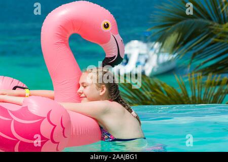 Portrait of teenage girl hugging son flamand rose dans la piscine à débordement en hôtel de luxe, Punta Cana, République dominicaine. Vacances d'été Banque D'Images