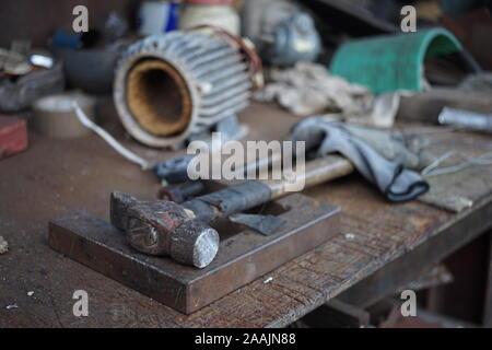 Ancien marteau avec un manche en bois enveloppé dans du ruban électrique sur un bureau, de menuisier. Outils de garage Banque D'Images