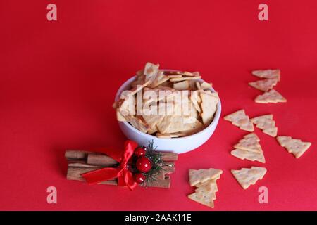 Edition 2019 Treeselets Jacobs, en forme d'arbre de Noël / chips crackers, basé sur Cheeselets, dans un bol avec un peu éparpillés sur fond rouge Banque D'Images