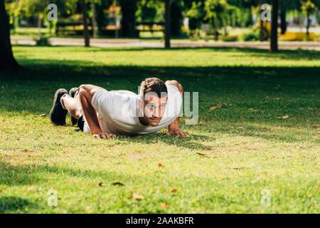 Concept de vie sain.La formation à l'extérieur.beau sport man doing pushups dans le parc sous le soleil de matin Banque D'Images