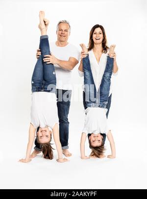 Les parents d'enfants jambes holding doing handstand, fond blanc Banque D'Images
