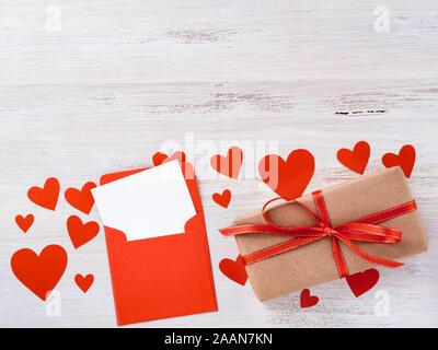 Symbole de la Saint-Valentin - boîte-cadeau en kraft papier marron avec ruban rouge, enveloppe avec une feuille de papier blanche et propre sur fond blanc avec beaucoup de Banque D'Images