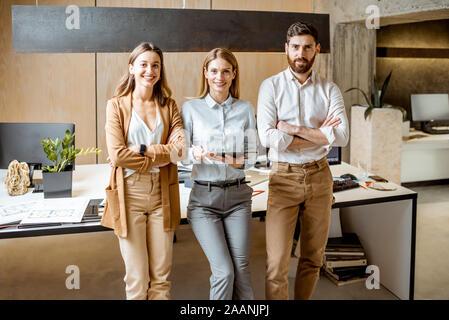 Portrait d'une équipe créative et confiante d'architectes ou designers debout ensemble dans le bureau moderne studio Banque D'Images
