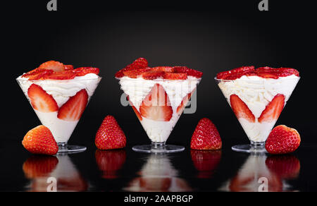 Les fraises avec de la crème en tasse sur fond noir Banque D'Images