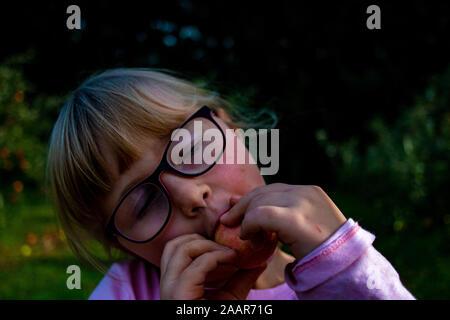 Cute little girl eating apple à la ferme. Vacances d'été à la campagne. Heureux l'enfant sur la nature. Funny kid jouit de l'extérieur au soleil. 24. Organique saine