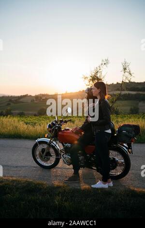 Jeune couple avec vintage moto standing on country road au coucher du soleil à la vue, en Toscane, Italie Banque D'Images