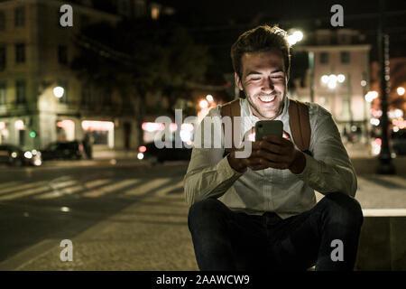Portrait of happy young man using cell phone in la ville la nuit, Lisbonne, Portugal Banque D'Images