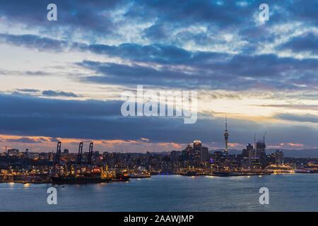 Les bâtiments modernes par mer contre ciel nuageux au crépuscule dans Auckland, Nouvelle-Zélande