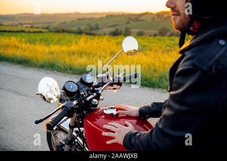 Petit coup de l'homme sur sa moto vintage au coucher du soleil, Toscane, Italie Banque D'Images