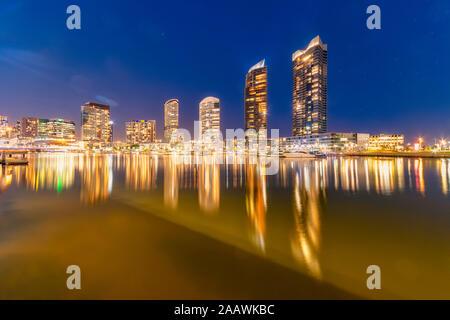Les bâtiments illuminés par la rivière Yarra à Docklands contre ciel, Melbourne, Australie
