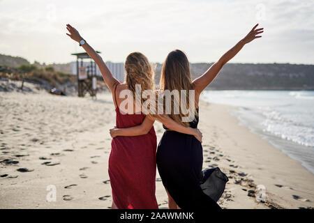 Deux jeunes femmes se tenant debout dans les bras sur une plage avec des bras outstreched