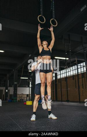 Jeune femme sautant à anneaux de gymnastique, l'homme aide sa Banque D'Images