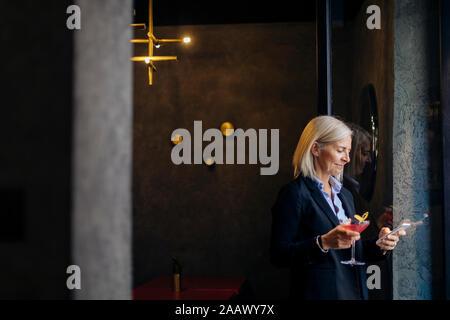 Femme d'âge mûr en prenant un cocktail après le travail, using smartphone