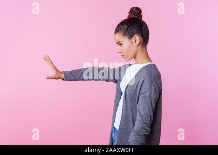 Stop! Vue latérale d'une adolescente avec bun hairstyle dans les tenues de l'article montrant la main posée avec interdiction Interdiction geste bloc avec palm, Banque D'Images