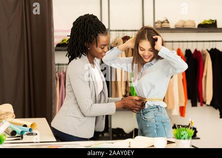 Couturière Afro Girl Measuring waist du Client travaillant dans l'Atelier de couture Banque D'Images