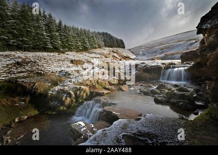 Ruisseau de montagne avec de petites chutes de neige de l'hiver et ciel dramatique
