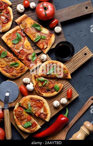 Flatlay abondante de pizza végétarienne partie. Pizzas maison rustique avec champignons, tomates et basilic servi avec du vin et des légumes crus sur oak board Banque D'Images