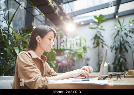 Side view portrait of smiling young woman using laptop in outdoor cafe terrasse décorée de plantes, copy space Banque D'Images