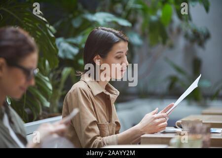 Side view portrait of young businesswoman reading documents tout en travaillant dans un café en plein air, copy space