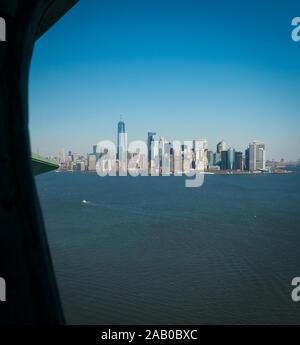 Manhattan skyline et Bay avec des bateaux de croisière shot couronne de statue de la liberté aux beaux jours. Couronne de lady liberty partiellement visibles, ciel bleu clair Banque D'Images