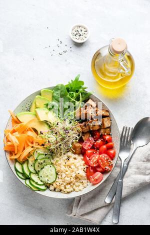 Bol à salade Vegan ou Bouddha bol avec des céréales, des légumes et du tofu. Vue supérieure, orientation verticale Banque D'Images