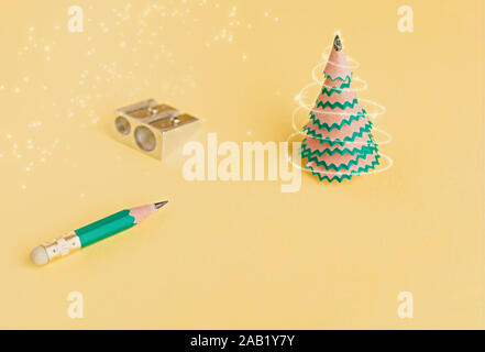 Arbre de Noël créatif. Copeaux de crayon, taille-crayon et sur un fond jaune. Concept de Noël dans le bureau. Focus sélectif. Close up. Banque D'Images