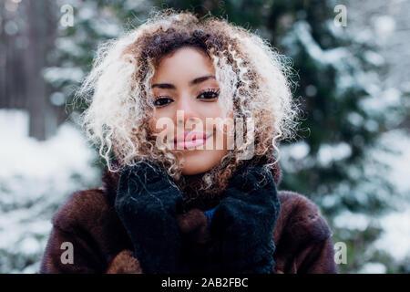 Belle jeune femme africaine dans l'hiver à l'extérieur. Concept d'hiver