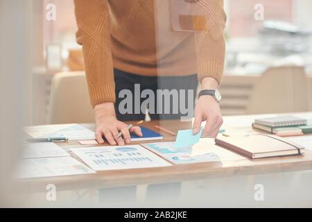 Cropped portrait of young businessman classement des documents et des données lors de la planification de projet derrière le verre wall in office, copy space