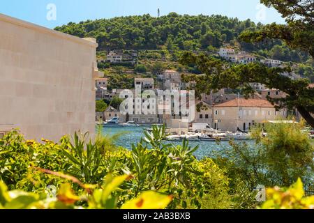 La ville de Supetar Brac en Croatie, vue de la mer sur une journée ensoleillée en été. Petit endroit idyllique de verdure. Village de Dalmatie, calme et peacef Banque D'Images
