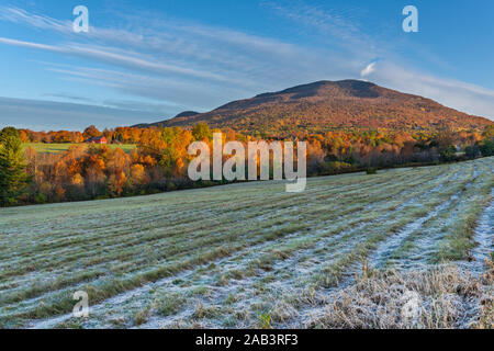 Vue d'automne sur le feuillage coloré, les montagnes et le champ de foin avec gel et une ferme rouge à Manchester, Vermont.