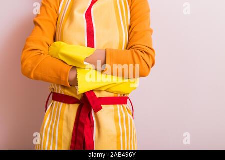 Image de femme au foyer avec les bras croisés en face de mur.