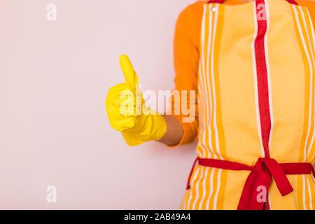 Image de femme au foyer showing thumb up en se tenant debout en face de mur.