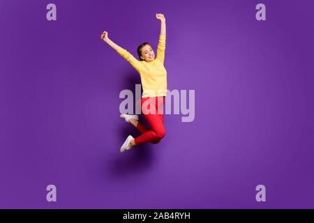 Longueur totale de la photo jolie teen dame haut saut célébrant vacances sensibilisation Haut les mains porter des pantalons décontractés pull jaune violet rouge isolé