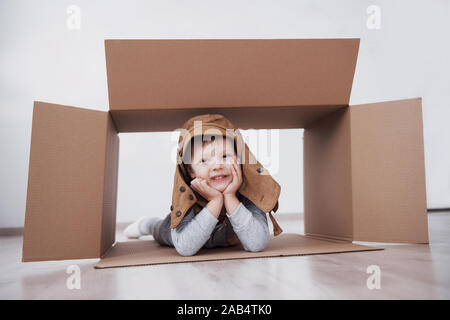 La petite enfance ludique. Petit garçon s'amuser grâce à la boîte de carton. Garçon prétendant être pilote. Little Boy and girl having fun at home