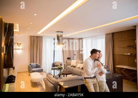 Couple debout dans la salle de séjour d'un appartement contemporain