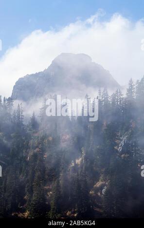 La dérive des nuages bas à travers la forêt et les montagnes près de Snow Lake at Snoqualmie Pass en cascades de l'état de Washington, USA. De l'automne. Banque D'Images