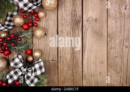 Du côté de Noël blanc et noir avec bordure vérifiée buffalo plaid ruban, décorations et les branches d'arbres. Vue de dessus sur un fond de bois rustique.