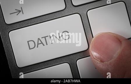 Un homme en appuyant sur une touche du clavier d'un ordinateur avec le mot datant, datant de l'ordinateur image concept. Banque D'Images