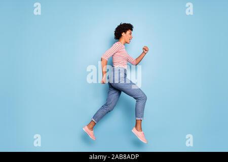 Profil de côté toute la longueur de la taille du corps photo de Happy cute positive assez belles amie portait un jeans denim chemise rayée chaussure running