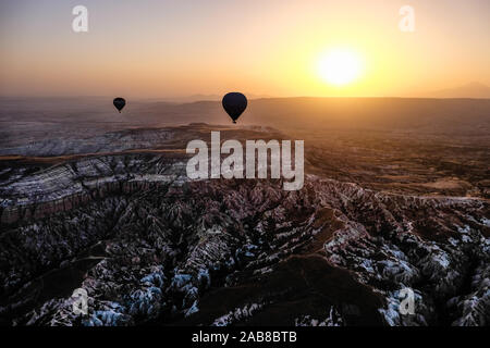 Silhouetté montgolfières au lever du soleil sur les montagnes en Cappadoce Banque D'Images