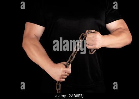 Homme adulte de noir se tient debout avec les muscles tendus et est titulaire d'une chaîne en métal rouillé, notion de force et d'endurance. Banque D'Images