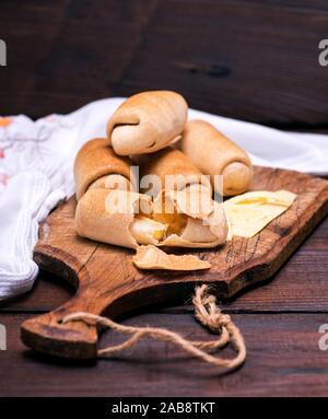 Des galettes cuites au four avec du fromage sur une planche de bois brun. Banque D'Images
