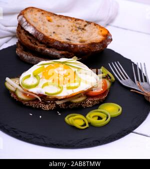 Avec Sandwich œuf frit et un morceau de pain de seigle avec des légumes. Banque D'Images