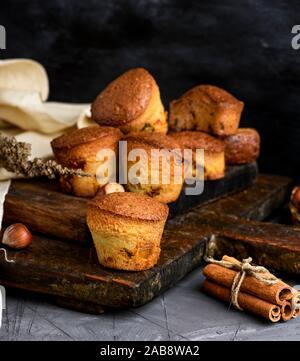 Des muffins ronde avec des fruits secs et raisins secs sur une planche de bois brun, noir table.